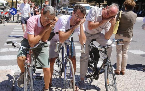 L'attesa  - Verona, ciclisti fanno un sonnellino sull'isola pedonale aspettando che venga il verde al semaforo di San Luca (foto Sartori)