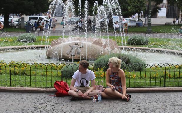 A Verona - Il cielo è plumbeo, e non si capisce se piove o non piove in questa Verona di inizio luglio. Due turisti si fermano e si interrogano sul da farsi (foto Fotoland)