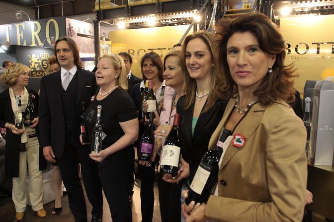 Il secondo giorno al Vinitaly. Donne del vino con bottiglia di grappa unità d'Italia