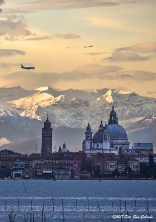 Lo splendido scatto di Gino Gabrieli che ha immortalato un aereo mentre sorvola Venezia, con le Alpi imbiancate sullo sfondo