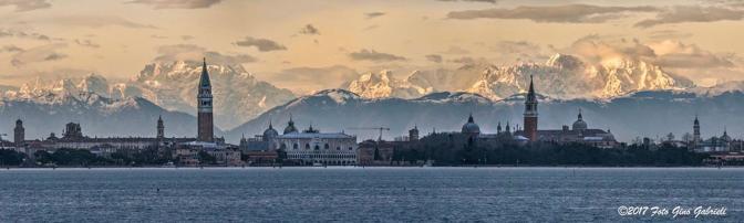 Una delle meravigliose foto di Gino Gabrieli. In primo piano la magia di Venezia e sullo sfondo la bellezza delle Alpi innevate