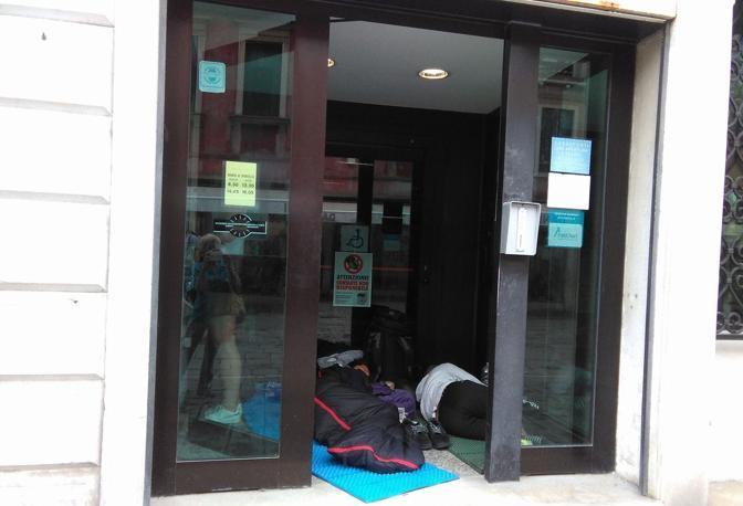 Turisti addormentati nel sacco a pelo all'interno dello sportello bancomat