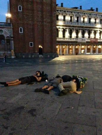 Turisti sdraiati in piazza San Marco